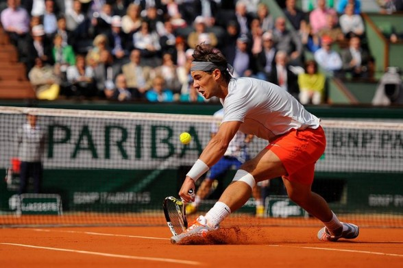 rafael nadal digging in clay court for fabio fognini bare tennis back action 2015
