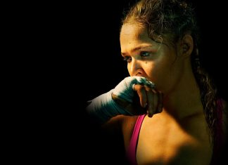 """ESPN is pushing their piece on Ronda Rousey in the December issue of ESPN The Magazine. Big time. Ramona Shelburne got the first interview with the former UFC Bantamweight Champion after the devastating knockout at the hands of Holly Holm in November. The piece is featured on the front page of ESPN even as the NFL playoffs are just weeks away. Rousey, even in defeat, is an enormous draw to even the casual sports fan. The interview gives us some insight on how Rousey is dealing with the fact that she will not retire from the UFC undefeated. Holm made sure of that with a nasty head kick that rendered the """"Most Dangerous Unarmed Woman in the World"""" defenseless and unconscious. The fighter knows all too well just how happy her loss made many people. Rousey made a ton of enemies as she became more and more outspoken leading up to her battle against Holm. Not touching gloves with her opponent at UFC 193 enraged even the likes of Donald Trump and Lady Gaga, not exactly fight fanatics. Rousey was regularly disrespectful of Holm who conducted herself like a true sportsman. It's one thing to come out verbally swinging against trash like Kim Kardashian and Floyd Mayweather. Any normal person can get behind that. I loved her for it! Yet when Rousey took her trash talking next level against a decent person like Holly Holm, she actually lost some fans and gave her haters even more ammo. Rousey knows exactly what her haters are saying about her…..""""That I'm a fucking failure and I deserve everything that I got,"""" she says sharply. It's good that she recognizes that. No need to hide from the hate. It's true and largely constructed by her, much of it purposely to grow her brand. Hard to get attention in a male dominated sports world by being goody goody all the time. Gotta stand out if you want to be the centerpiece on ESPN's front page. What has Rousey done since the loss? According to the ESPN article, she has isolated herself for the most part. Feeling embarrassed, physically hurt """