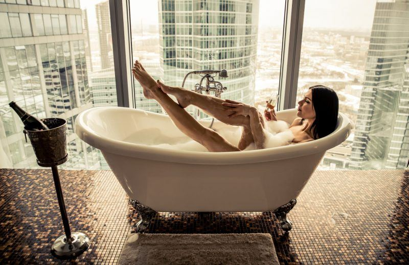 woman enjoying bath top of world before boyfriend comes