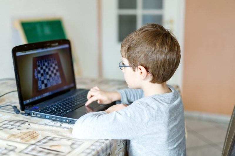 young boy playing online chess on laptop
