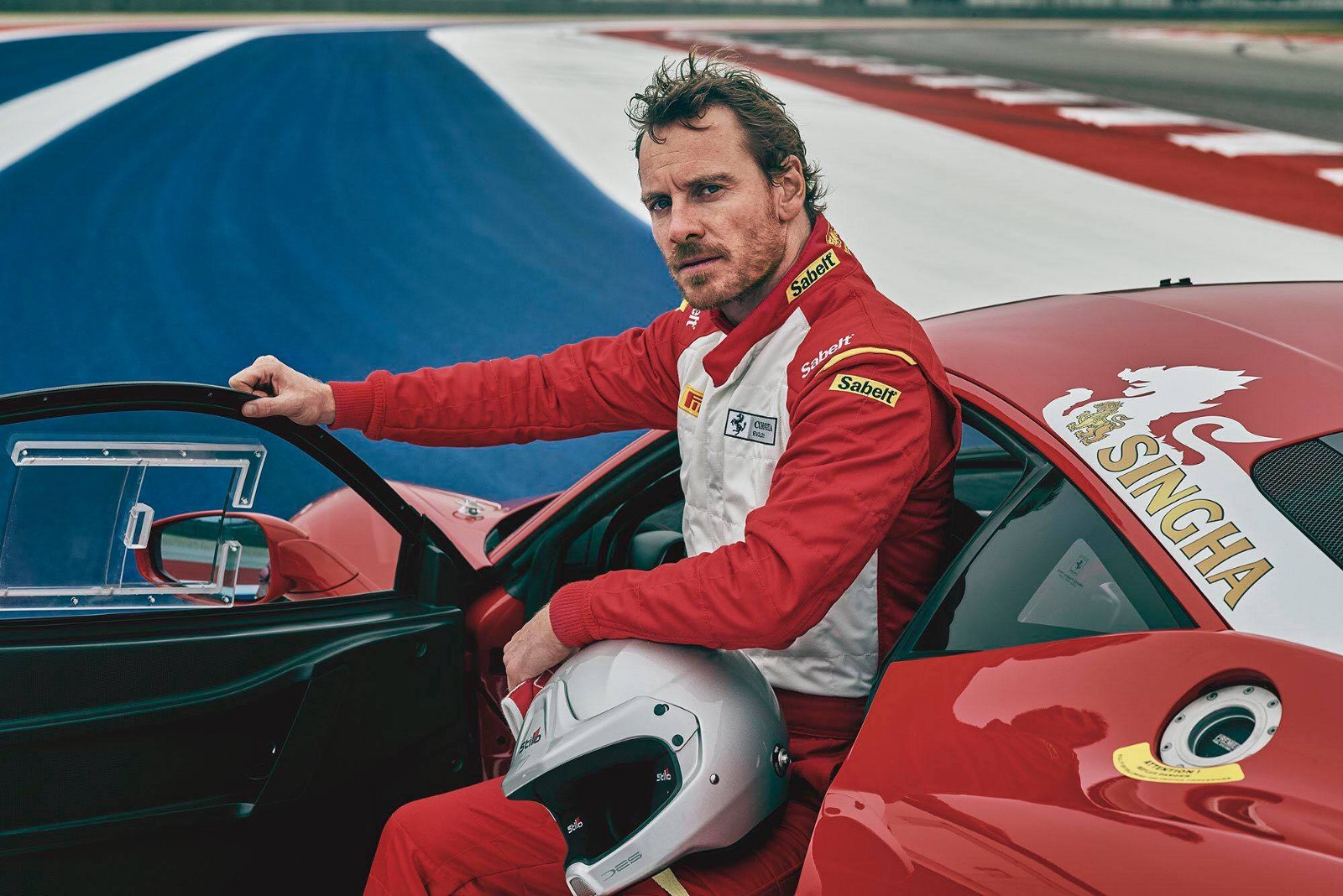 michael fassbender sitting in red race car