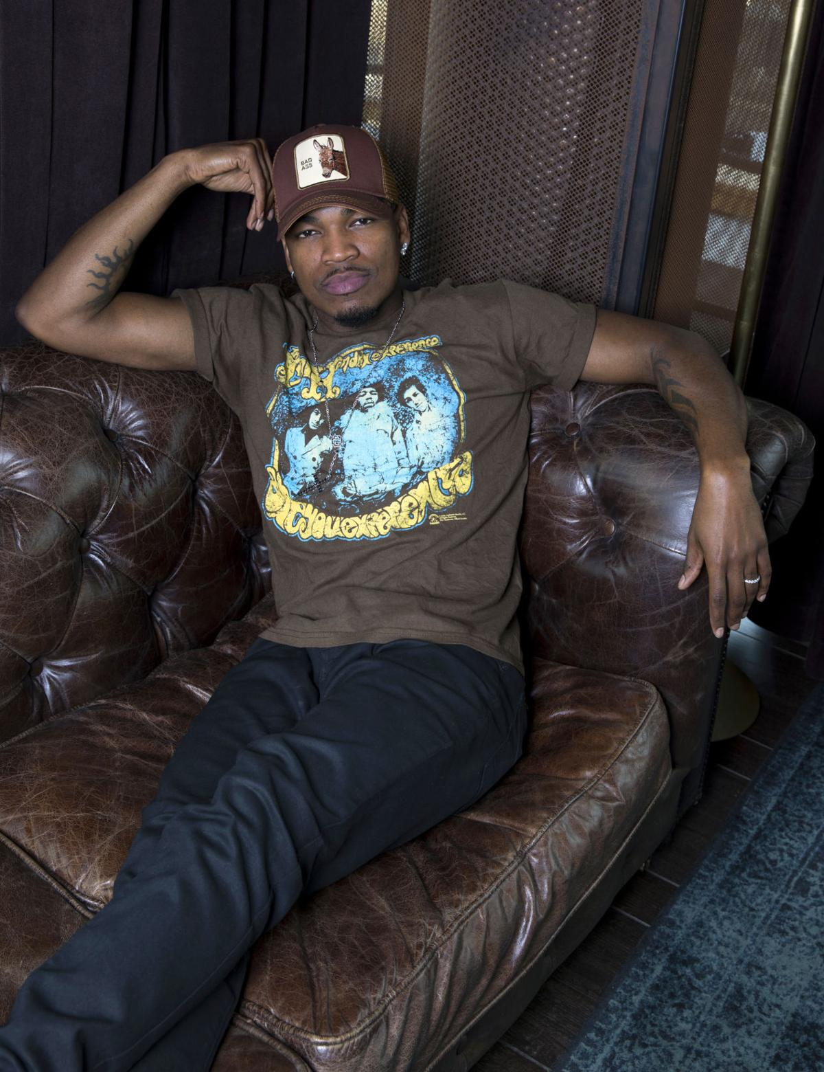 ne yo sprawled out on hot leather bulge sofa
