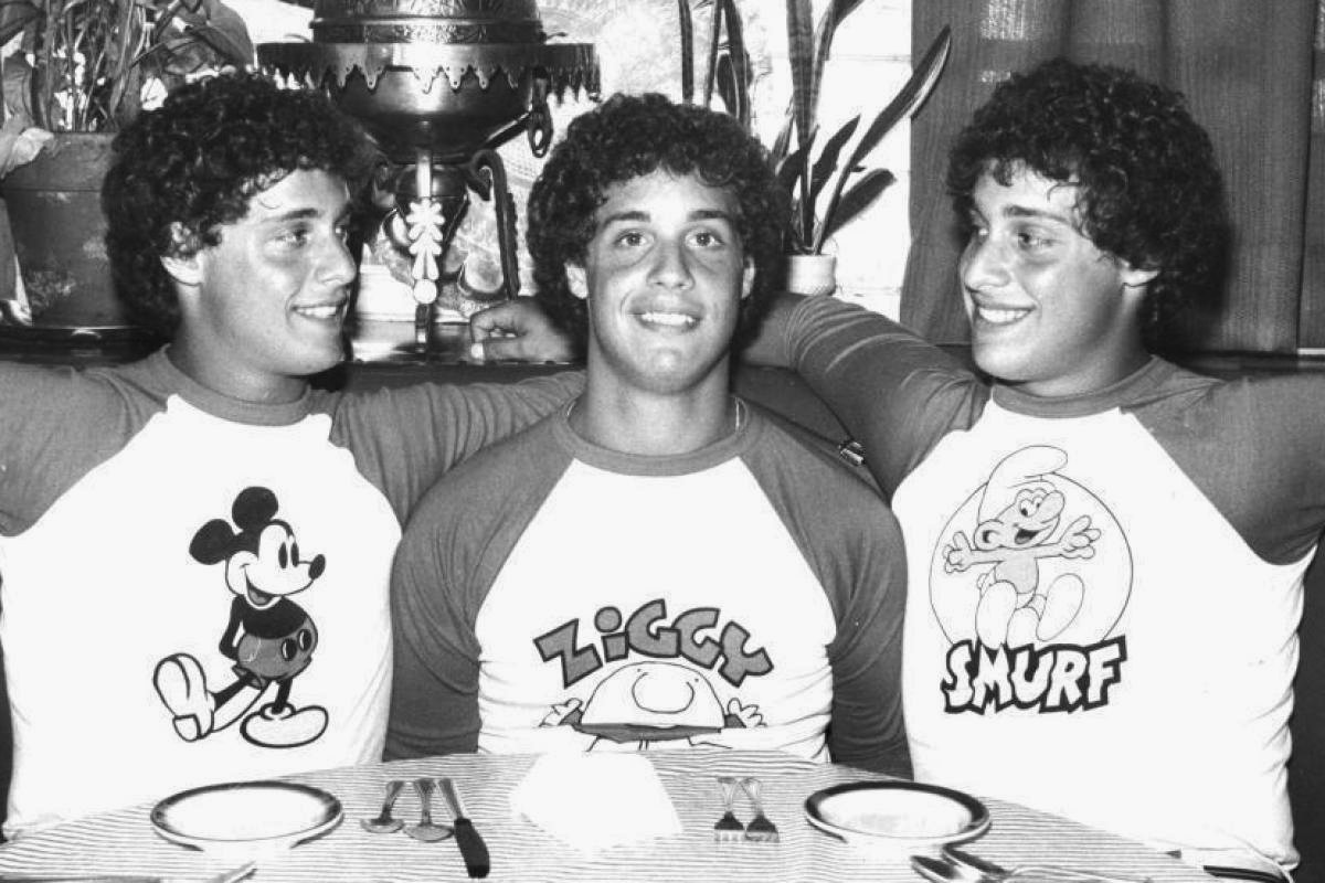 three identical strangers with mickey mouse shirts