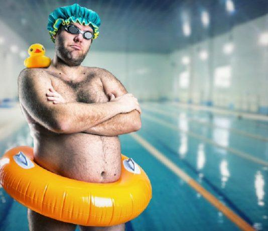 funny man with ducky on shoulder in pool ring around waist