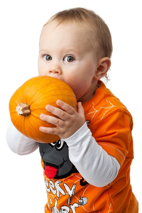 child biting into a pumpkin