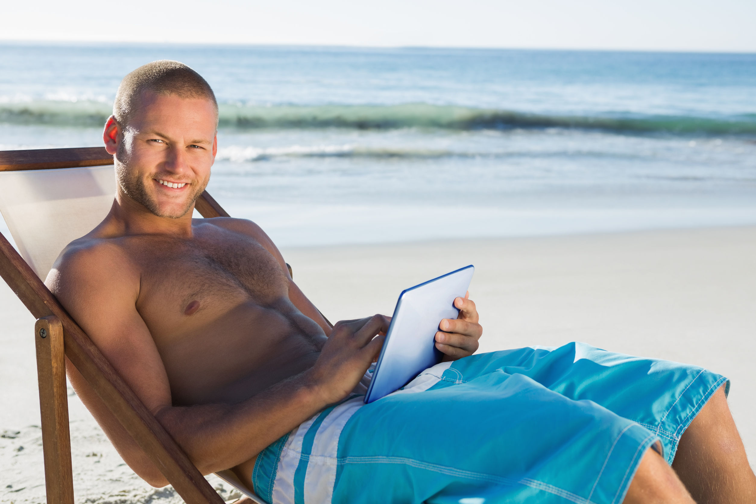 sexy guy shirtless at beach playing casino games