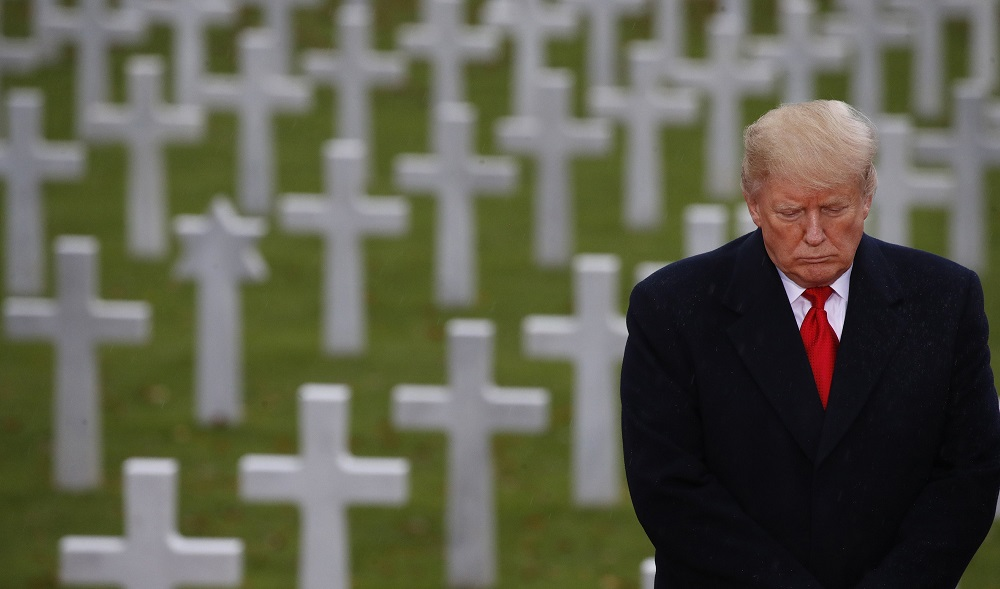 donald trump standing along in paris headstones cemetary