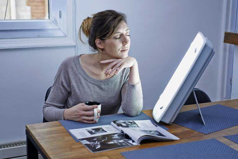 woman using lightbox to fight sad seasonal affective disorder