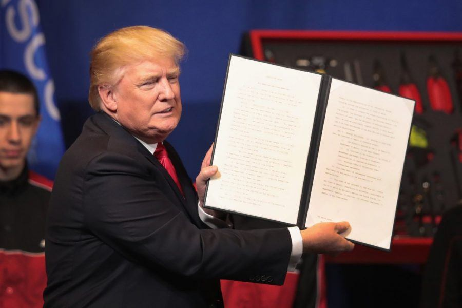 Donald Trump showing off latest immigration crackdown signed bill.