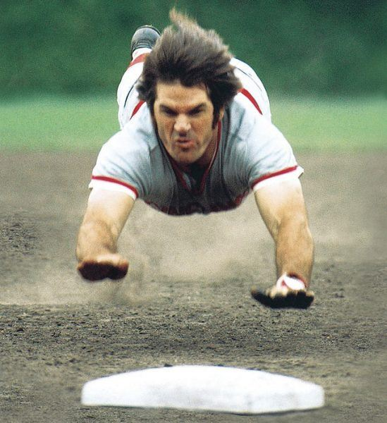 Pete Rose sliding into home base while caught lying.