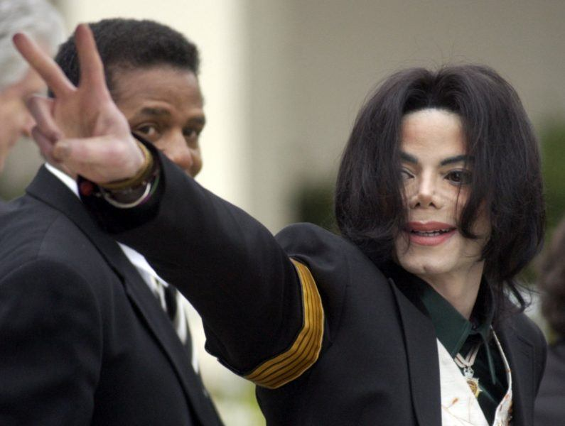 Michael Jackson waves to fans at court during child molestation charges.