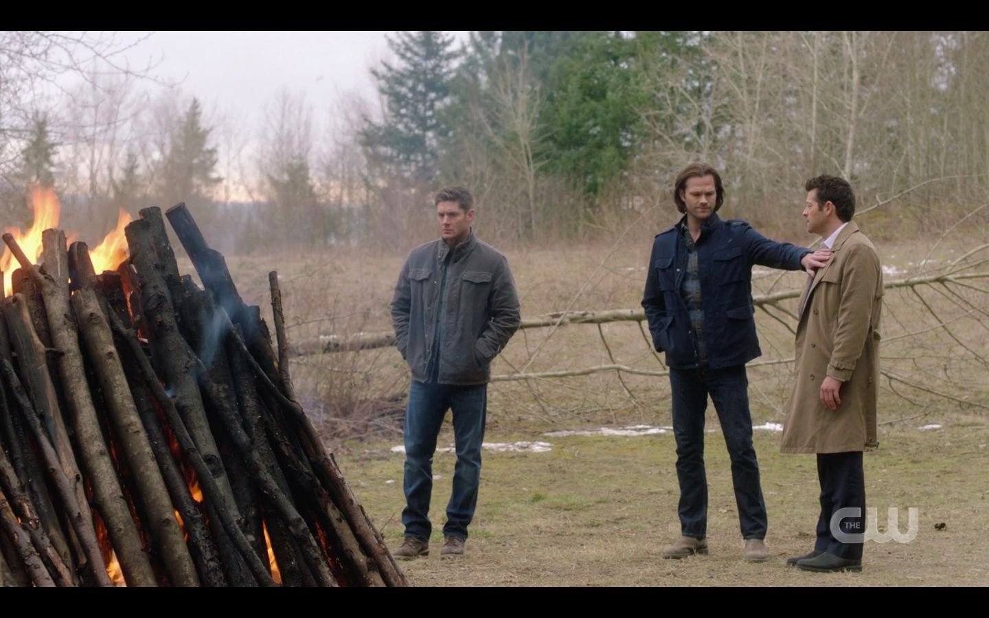Castiel tries to go to him to offer comfort, but Sam Winchester puts out a hand and stops him, shaking his head as fire burns.