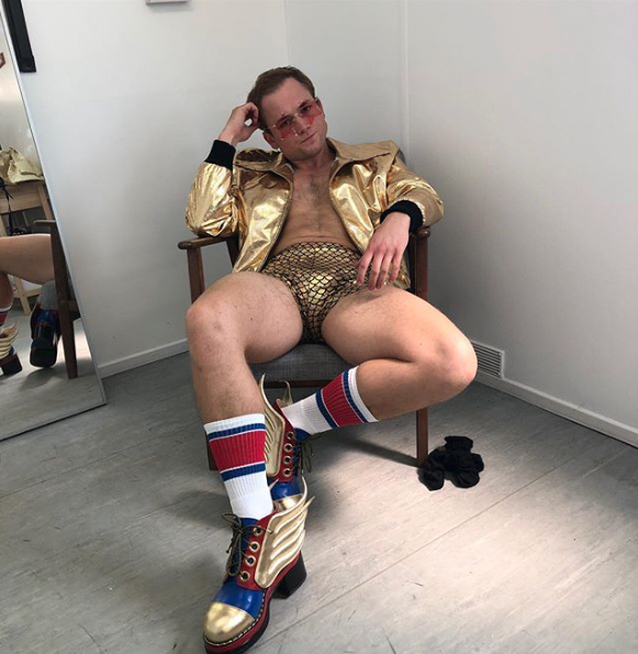 Taron Egarton in tight gold shorts shirtless for Elton John Rocket Man movie.