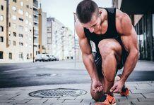sexy fit man tying nike running shoes wearing wireless headphones app