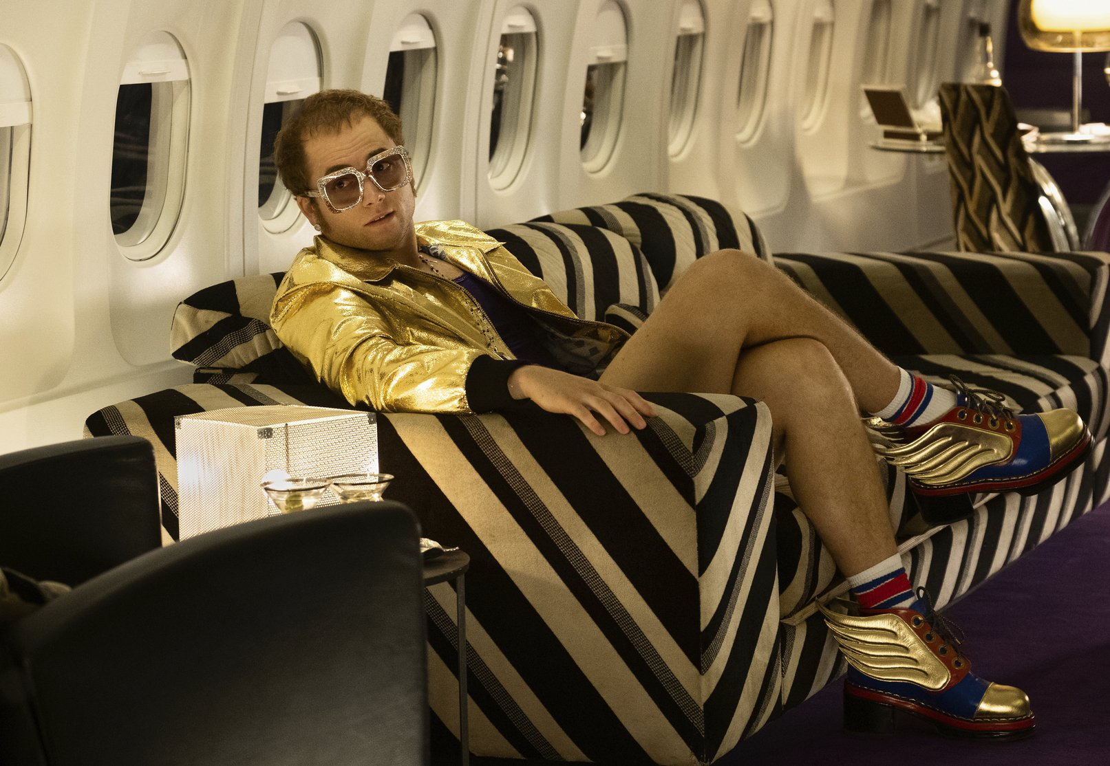 taron egerton shorts in rocketman biopic on elton john images on plane