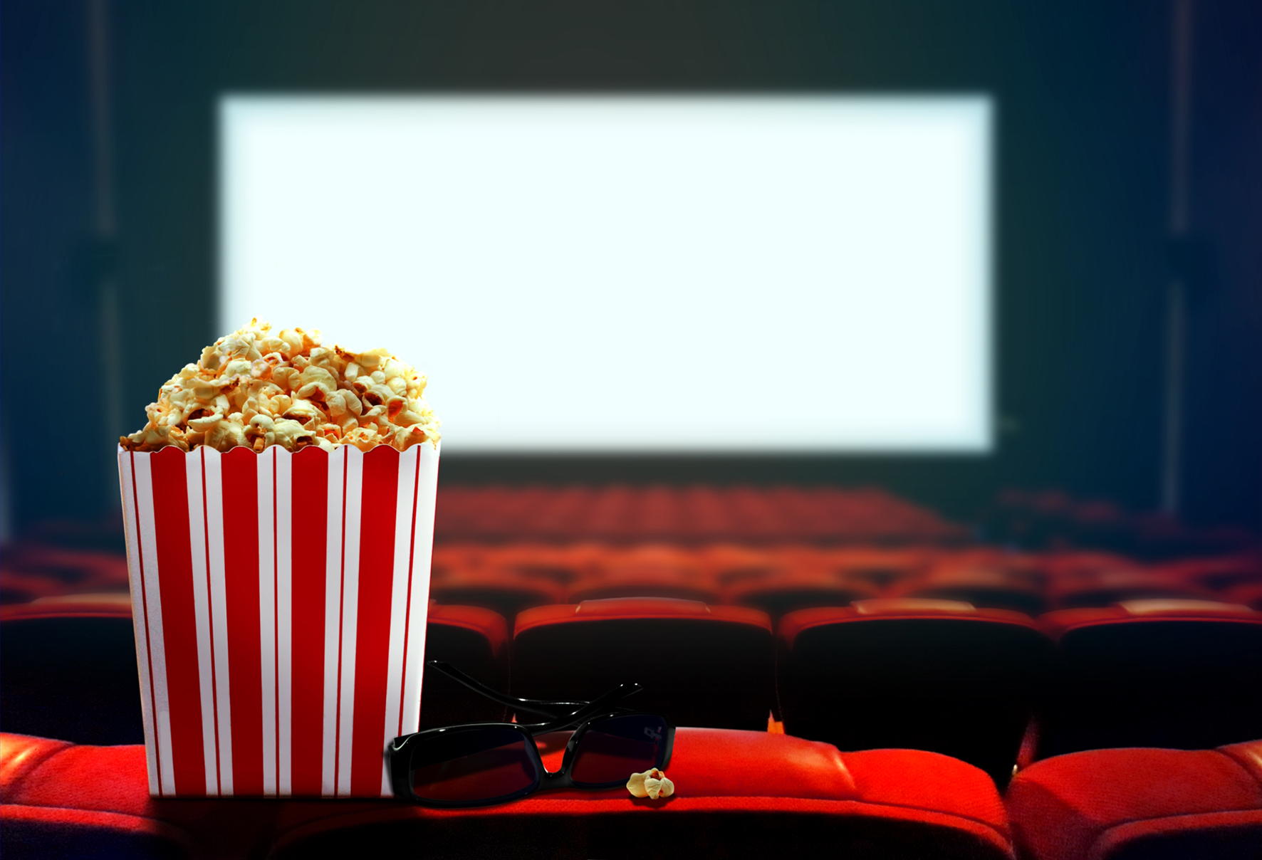 box of popcorn sitting in front of theater movie screen
