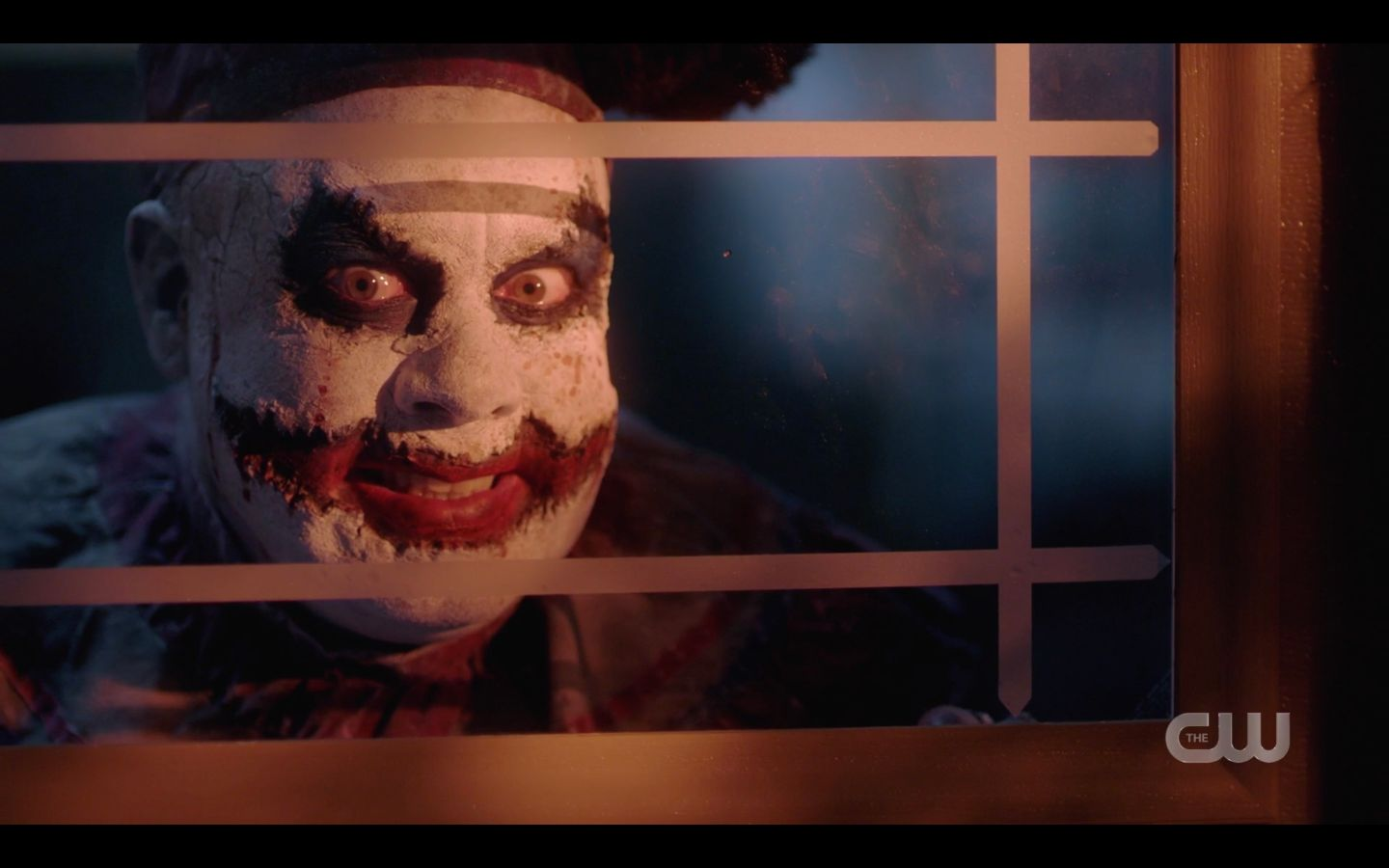 Creepy clown Belphigor looking out window at Sam Winchester SPN 1501
