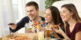 Friends watching tv and eating pizza