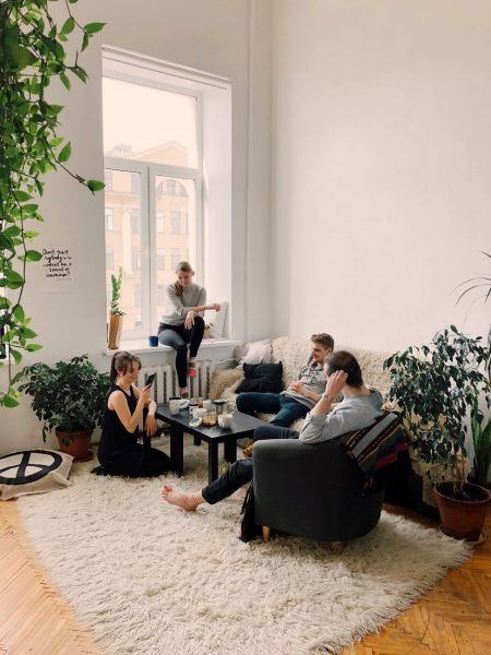 young men women rommates hanging out in white plant filled apartment