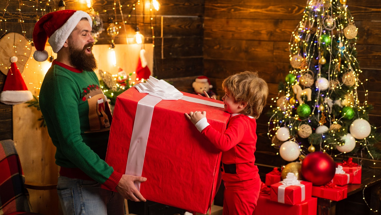 Cute little child with parent is decorating the Christmas tree indoors. Home Christmas atmosphere. Christmas kids with gift emotion - happiness concept.