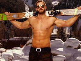 shirtless guy with sunglasses and skis over shoulder outside in winter