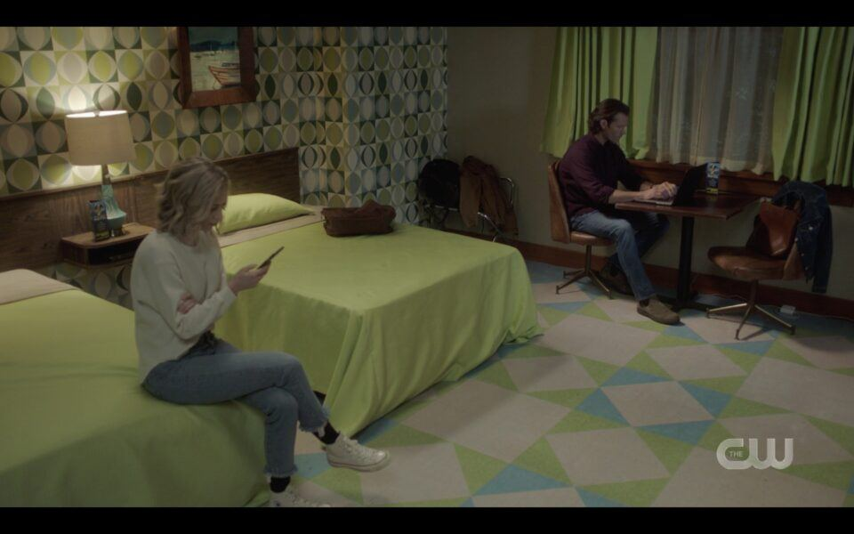 Sam Winchester researcing in motel room with Caitlin on Bed SUpernatural