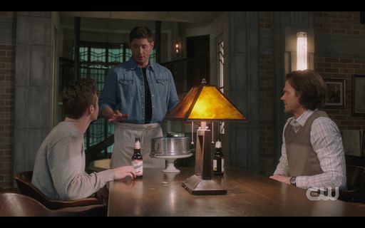 Dean Winchester bringing Jack a birthday cake with Sam.