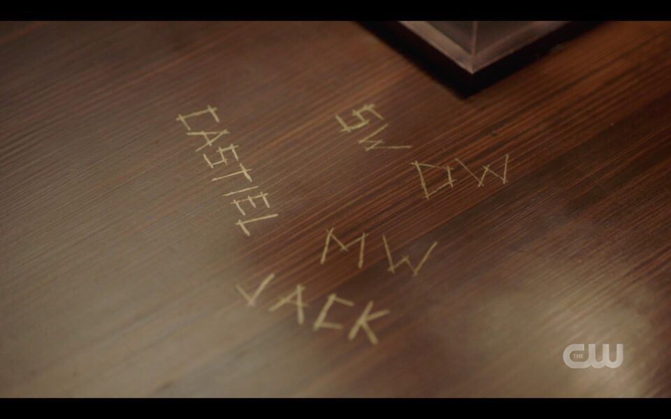 SPN finale Sam Winchester looks at initials carved in table