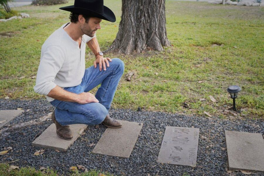 Walker Jared Padalecki looking at family handprints in stones leading to house
