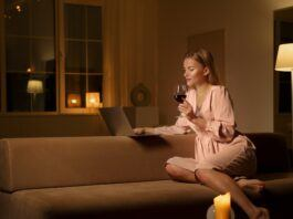 woman sitting on beige couch with glass of red wine for valentines day movies 2021