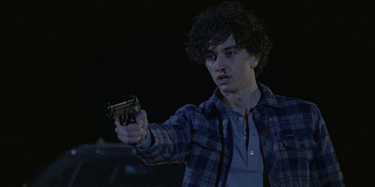 WAlker Trevor holding gun on bad guy.
