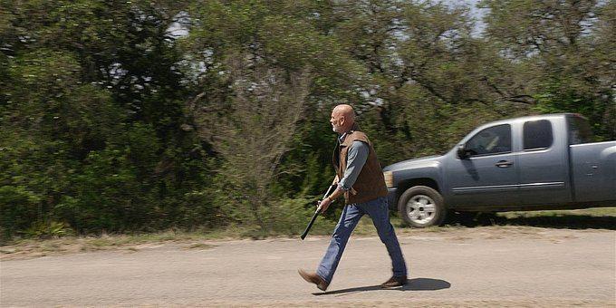 Walker Bonham walking with a shotgun ready to fire.