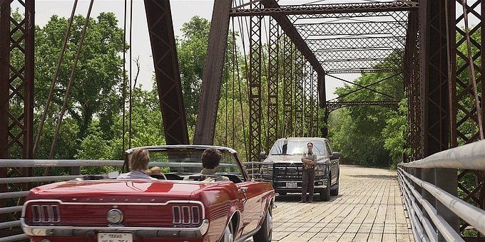 WAlker Micki blocking Cordell and Hoyt in red convertible on bridge.
