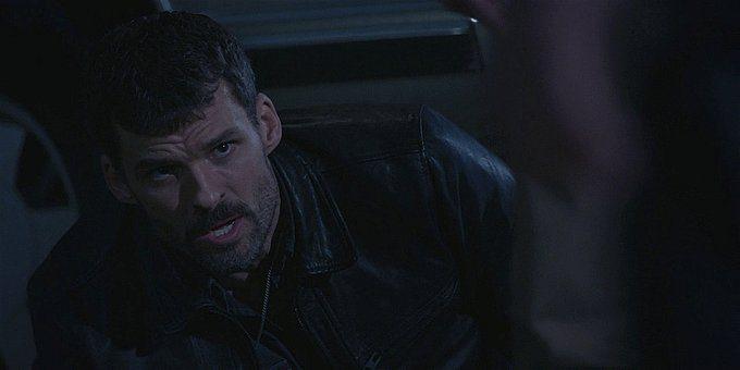 Walker Clint looking up at Micki holding gun on him.
