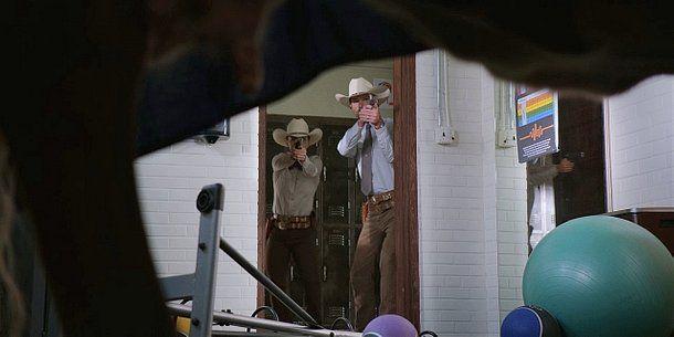 Walker Cordell Micki holding guns on cow in Wolverine drape.