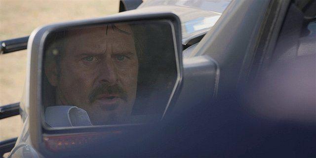 Walker STan looking in side truck mirror.