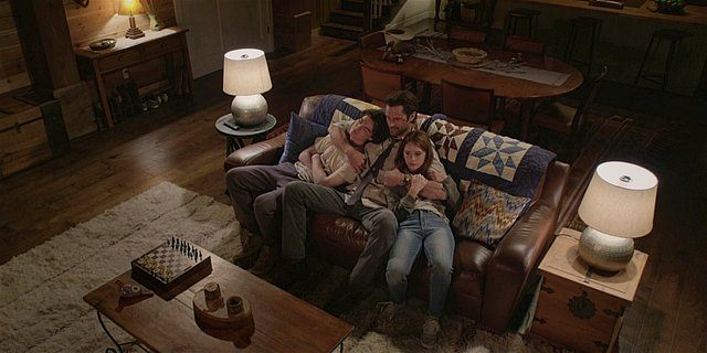 Walker Cordell with arms wrapped around Augie and Stella on couch.