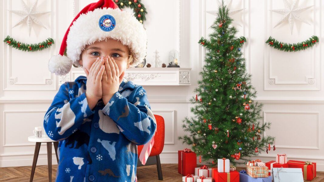young boy in santa hat excited with christmas gift guide 2021